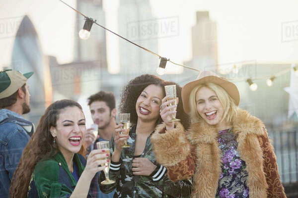 Portrait enthusiastic young women drinking champagne at rooftop party Royalty-free stock photo