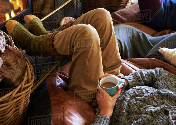 Boy drinking cup of coffee by fire Royalty-free stock photo