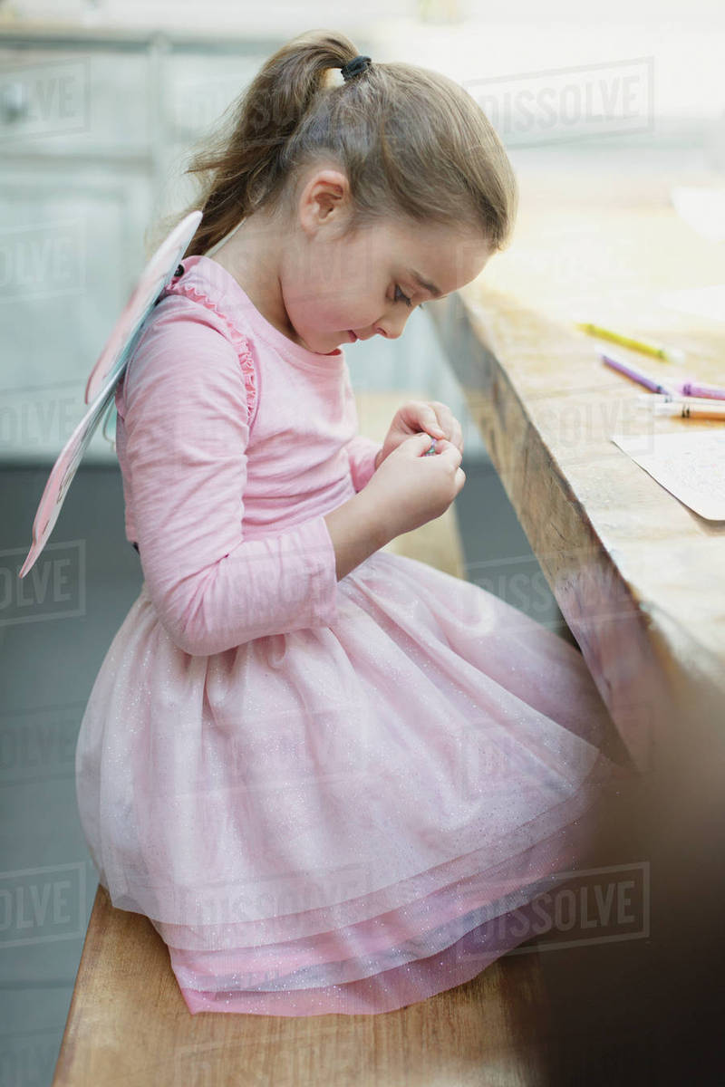 Girl in fairy wings coloring at dining table Royalty-free stock photo