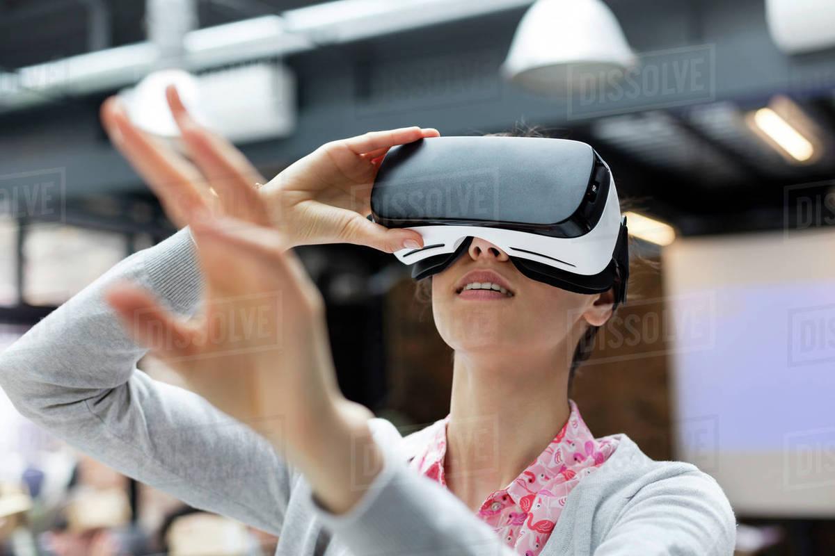 63685b204c4 Woman trying virtual reality simulator glasses glasses reaching ...