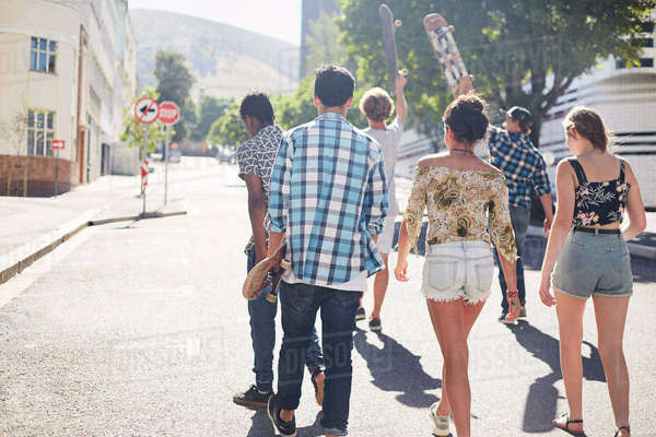 Teenage friends with skateboards walking on sunny urban street Royalty-free stock photo