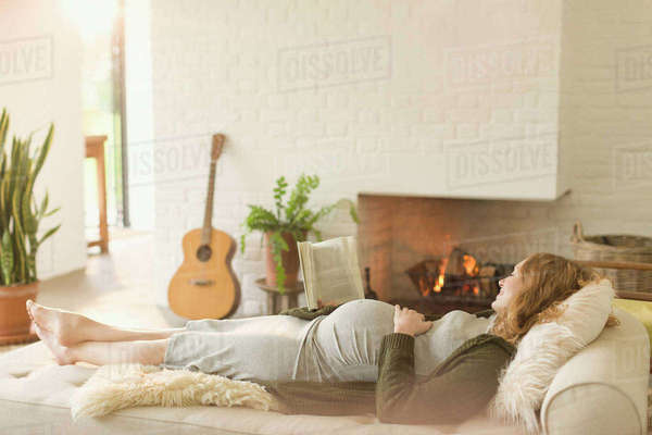 Serene pregnant woman laying on chaise next to fireplace in living room Royalty-free stock photo