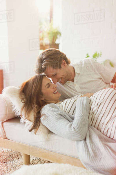 Pregnant couple laying and talking on chaise Royalty-free stock photo