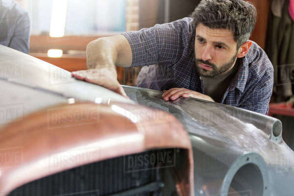 Focused mechanic examining classic car panel in auto repair shop Royalty-free stock photo