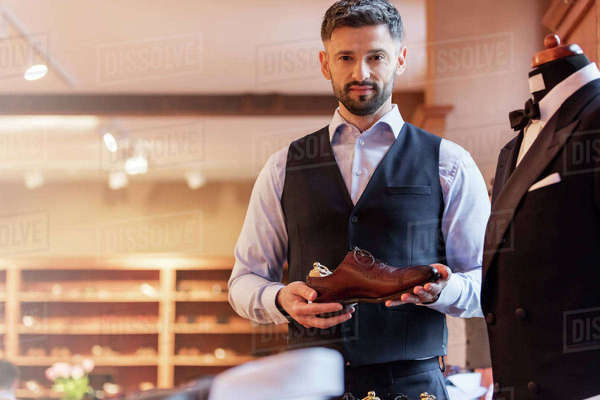 Portrait confident businessman holding dress shoe in menswear shop Royalty-free stock photo