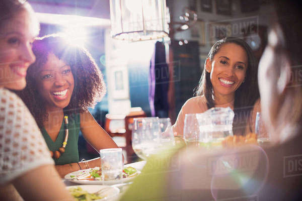 Smiling women friends dining talking at restaurant table Royalty-free stock photo