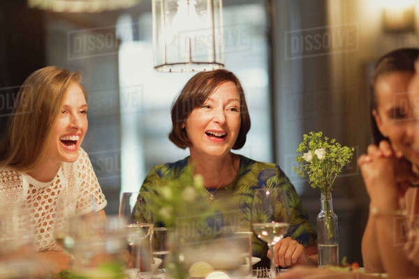 Laughing women friends dining and talking at restaurant table Royalty-free stock photo