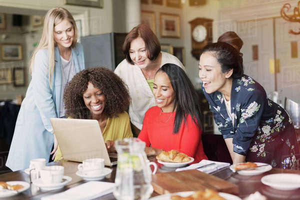 Smiling women friends using laptop at restaurant table Royalty-free stock photo