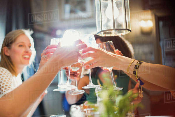 Smiling women friends toasting wine glasses dining at restaurant table Royalty-free stock photo