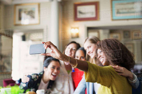 Smiling women friends taking selfie with camera phone in restaurant Royalty-free stock photo
