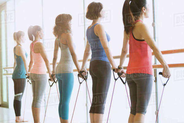 Women exercising with resistance bands at barre in exercise class gym studio Royalty-free stock photo