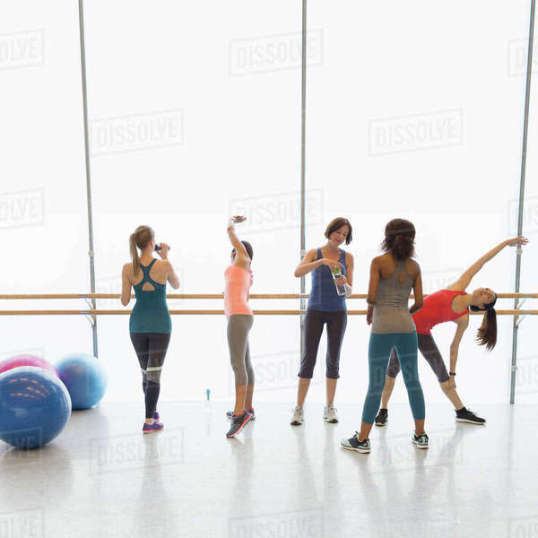 Women stretching and drinking water in exercise class gym studio Royalty-free stock photo