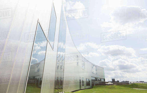 Modern building with reflection under sunny blue sky with clouds Royalty-free stock photo
