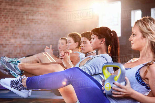Young men and women with kettlebells in exercise class gym studio Royalty-free stock photo
