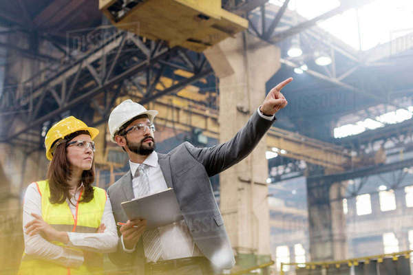 Manager and female steel worker talking looking away in factory Royalty-free stock photo