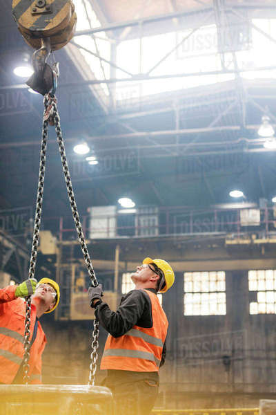 Steel workers looking up at crane chain in factory Royalty-free stock photo