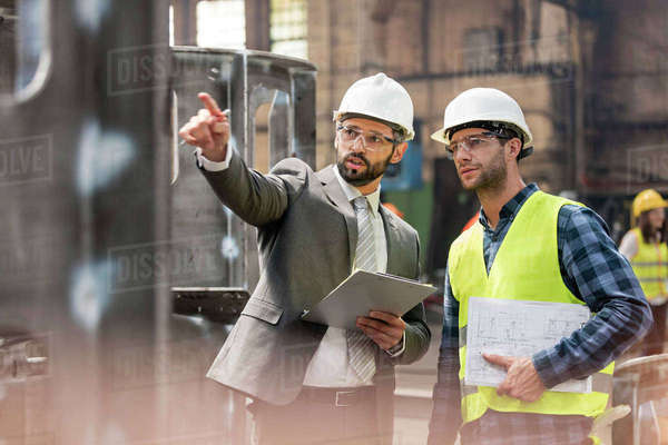 Manager and steel worker talking and looking away in factory Royalty-free stock photo