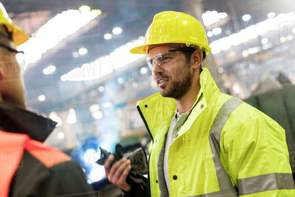 Steel workers talking in factory Royalty-free stock photo