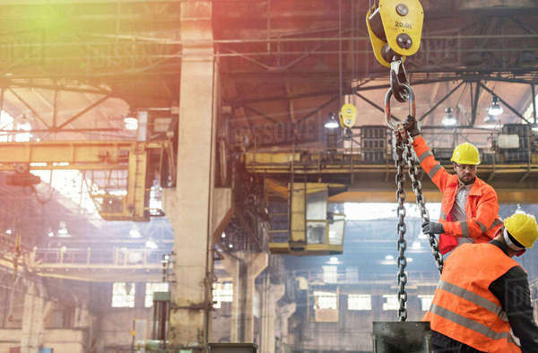 Steel workers operating crane in factory Royalty-free stock photo