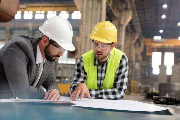 Manager and engineer reviewing blueprints in steel factory Royalty-free stock photo