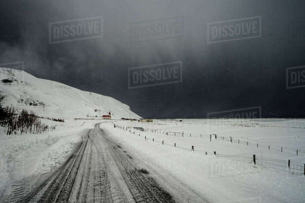 Road through snow covered landscape below stormy sky, Vik, Iceland Royalty-free stock photo