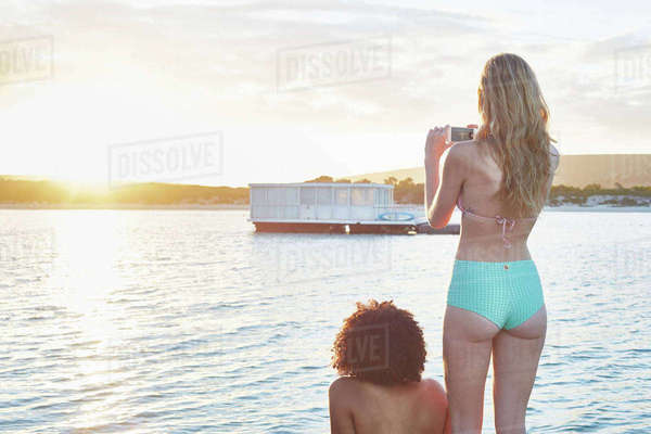 Young woman in bikini photographing houseboat on sunny summer ocean Royalty-free stock photo