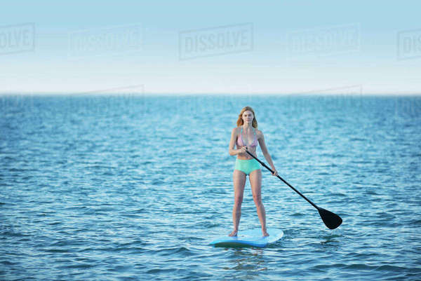 Young woman in bikini paddleboarding on summer ocean Royalty-free stock photo