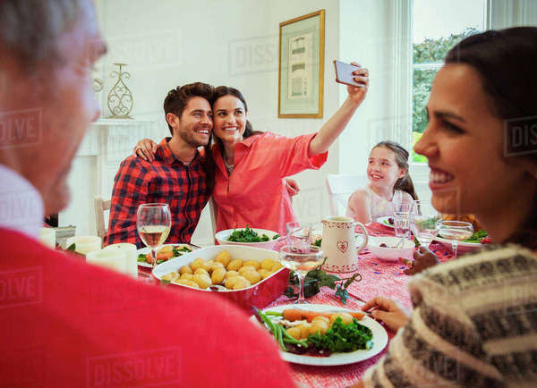 Couple with camera phone taking selfie at Christmas dinner table Royalty-free stock photo