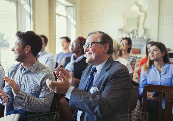 Smiling business people clapping in business conference audience Royalty-free stock photo
