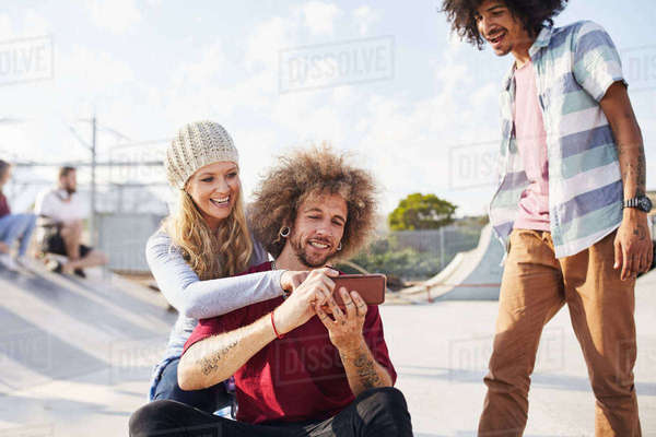 Friends using smart phone at sunny skate park Royalty-free stock photo