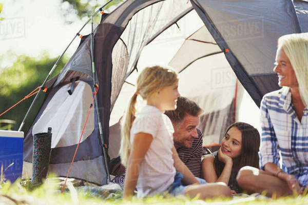 Smiling family talking and relaxing outside sunny tent Royalty-free stock photo