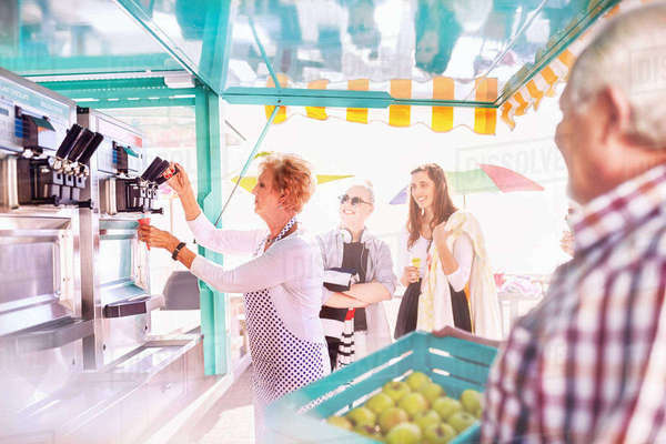Senior female business owner serving ice cream at food cart Royalty-free stock photo