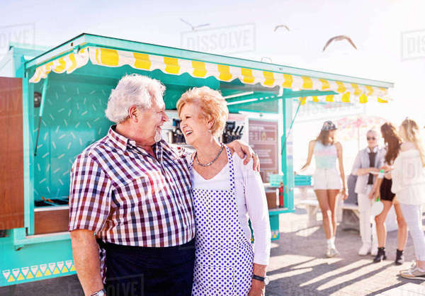 Smiling affectionate senior couple business owners outside sunny food cart Royalty-free stock photo