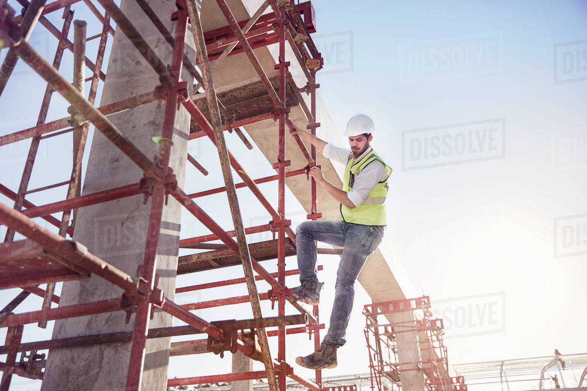 construction worker climbing rebar at sunny construction site