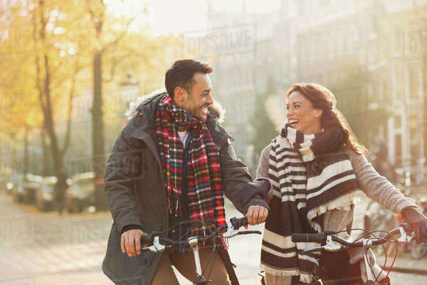 Smiling young couple in warm clothing bike riding on urban autumn street Royalty-free stock photo