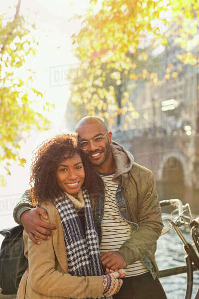 Portrait smiling, affectionate couple hugging along sunny autumn canal Royalty-free stock photo