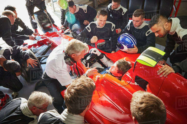 Manager and pit crew surrounding formula one driver in race car Royalty-free stock photo