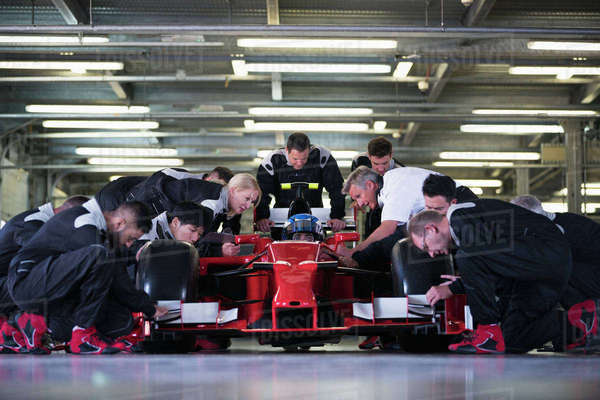 Pit crew preparing formula one race car and driver in repair garage Royalty-free stock photo