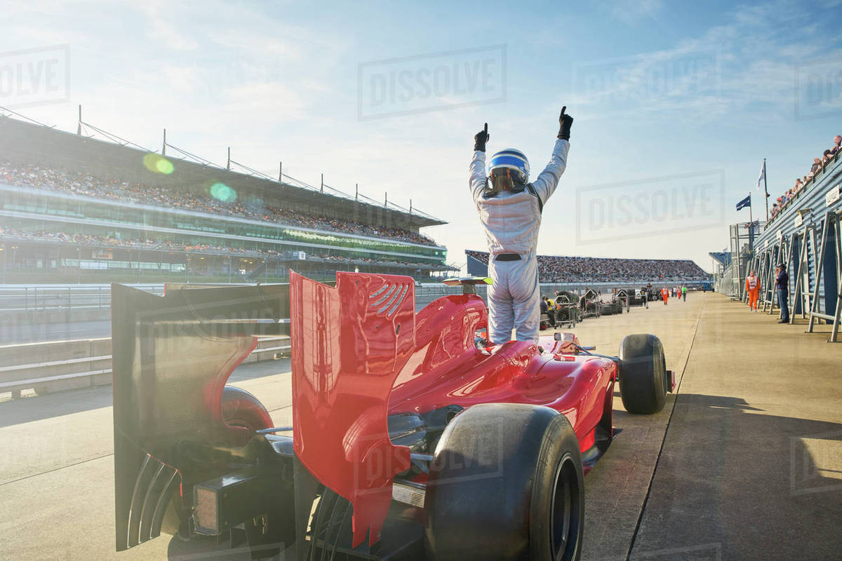 Formula one race car driver cheering on sports track, celebrating victory Royalty-free stock photo