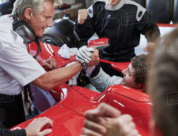 Manager and formula one race car driver handshaking, celebrating victory Royalty-free stock photo
