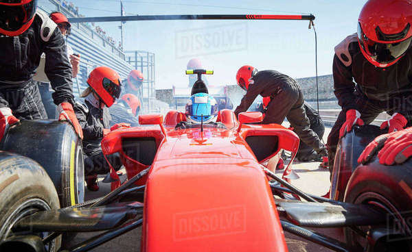 Pit crew replacing tires on formula one race car in pit lane Royalty-free stock photo