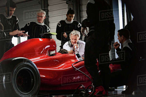 Manager and pit crew working on formula one race car in dark repair garage Royalty-free stock photo