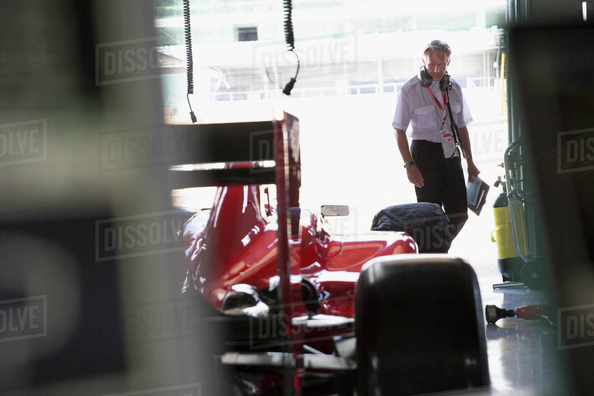 Manager examining formula one race car in repair garage Royalty-free stock photo
