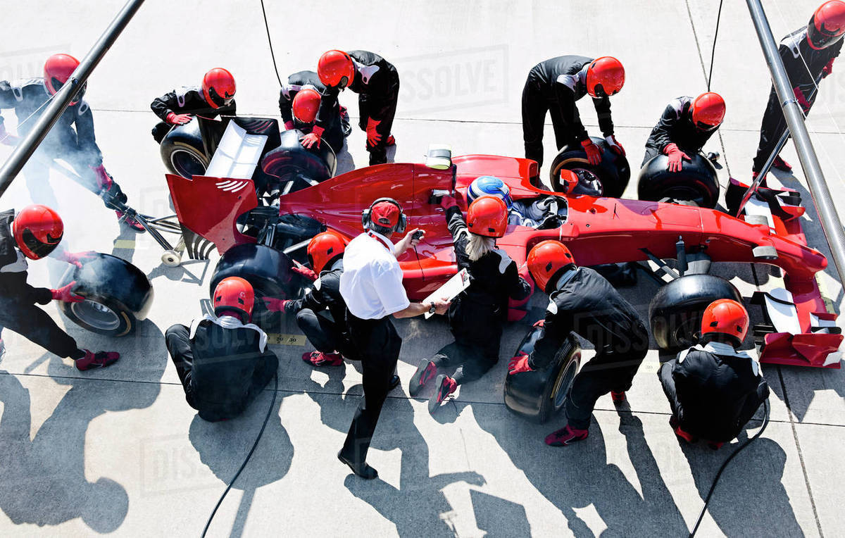 Manager with stopwatch timing pit crew replacing tires on formula one race car in pit lane Royalty-free stock photo