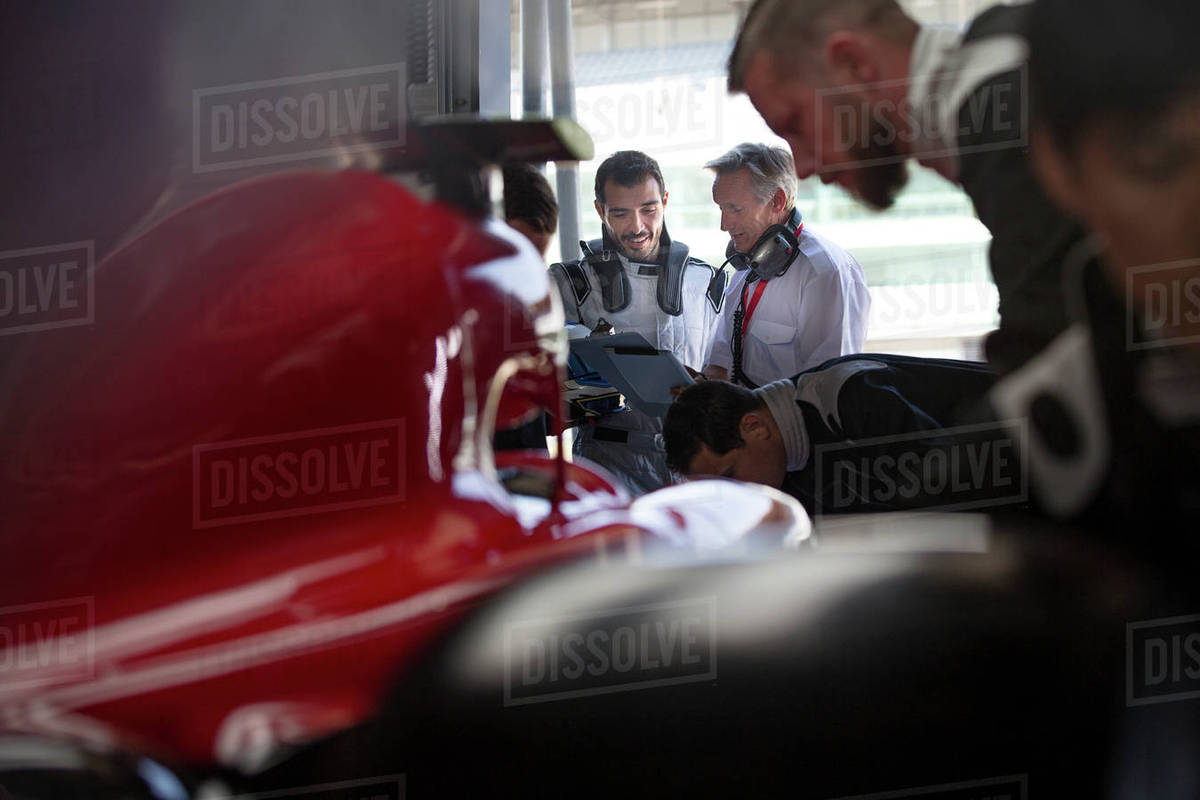 Manager and formula one race car driver talking in repair garage Royalty-free stock photo