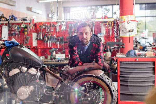 Portrait serious, confident motorcycle mechanic in workshop Royalty-free stock photo