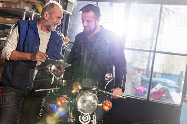 Motorcycle mechanic discussing paperwork with customer in shop Royalty-free stock photo