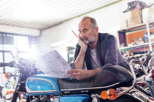 Focused senior male motorcycle mechanic reviewing manual in workshop Royalty-free stock photo
