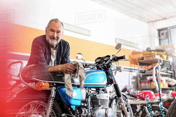 Portrait confident senior male motorcycle mechanic leaning on motorcycle in workshop Royalty-free stock photo