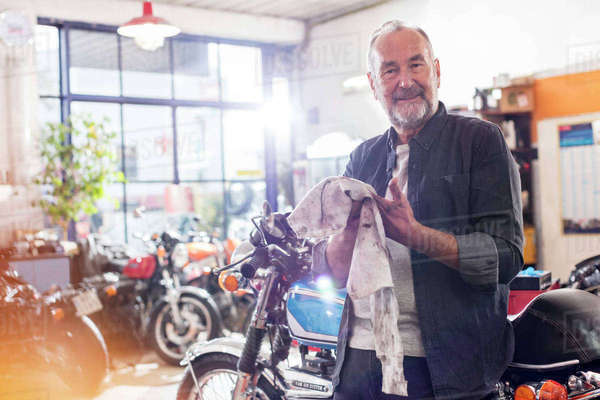 Portrait smiling senior male motorcycle mechanic wiping hands on rag in workshop Royalty-free stock photo
